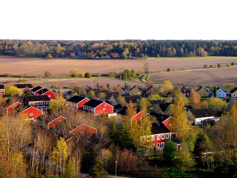 Peaked black rooftops on rows of distinctive red and yellow homes in Sweden
