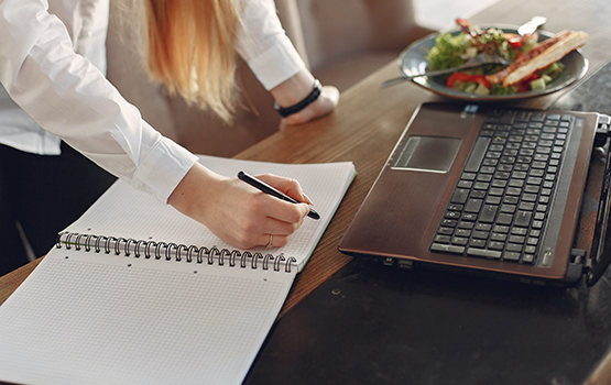 A woman with notepad, laptop and lunch