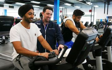 Monash sports trainer help gym user on machine