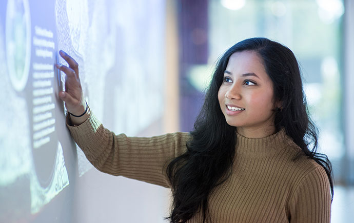 Student interacts with display foyer of Biomedicine Discovery Institute