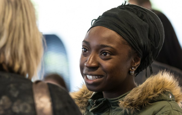 All four masters in the School of Media, Film and Journalism include a Research Pathway option which can lead to potential PhD study. Masters student stands smiling and talking to another person. She is wearing a khaki green jacket with fur collar and a head scarf.