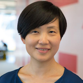 Dr Xin Gu, Senior Lecturer at Monash University is standing in a university facility, smiling at the camera and wearing a teal top. Her hair is short and swept to the side.