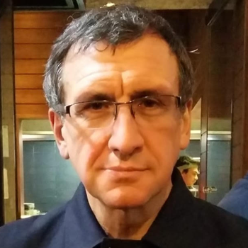 Paul Long, Professor in Master of Cultural and Creative Industries at Monash University is facing the camera. He is wearing clear-rimmed glasses, a black shirt and the background is a restaurant.